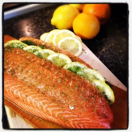 Soak cedar planks in water for approximately 20-30 min. Make sure to wash salmon and pat dry. Make a long thin slit with a sharp knife at a 45 degree angle along the top of the fillet. Gently layer in the the sliced citrus and fronds. Season Salmon with Salt, Pepper and Dill and Olive Oil.
